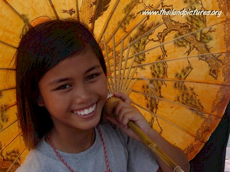 A young Thai girl holding a handpainted umbrella