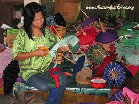 A Thai girl making small umbrellas in a factory.