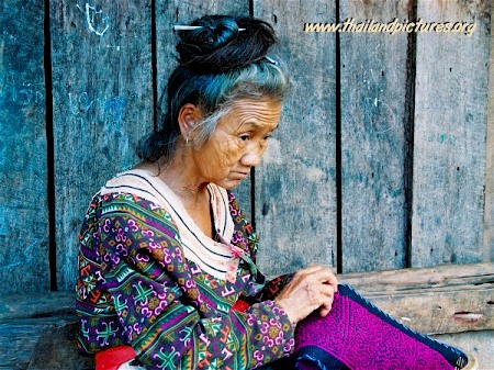 An old Thai woman sewing clothing.