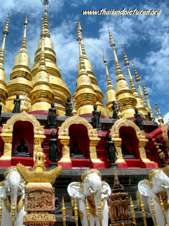 The golden thai temple with many towers and white elefants.